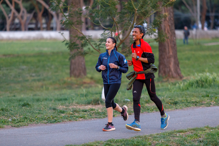 Rome, Italy - March 29, 2019: A man and a woman are jogging together in the greenery of the public, on a sunny spring day.