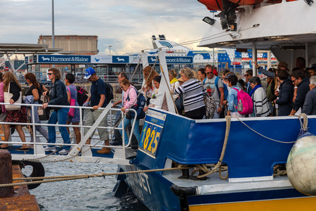 Naples, Italy - May 30, 2019: passengers get off the hydrofoil through the ladder that connects the boat to the port quay. Éditoriale