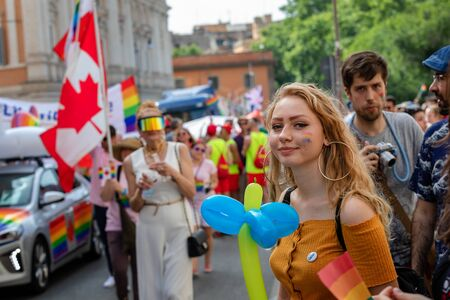 Rome, Italy - June 8, 2019: Gay Pride, public demonstration of the gay pride. A smiling girl in rainbow colors and an inflatable balloon manifests on the street with the crowd. Editorial