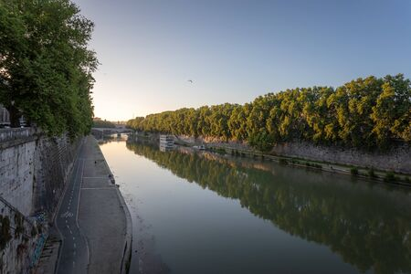 Panoramic view of the Tiber river with its imposing embankments and surrounding vegetation. At the bottom left the bike path that runs along the river.