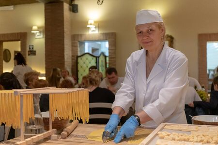 Rome, Italy - April 26, 2019: In a typical restaurant in the historic center a woman works handmade pasta. The woman prepares the dough and then cuts it and puts it to dry, ready to be consumed by the customers of the restaurant.