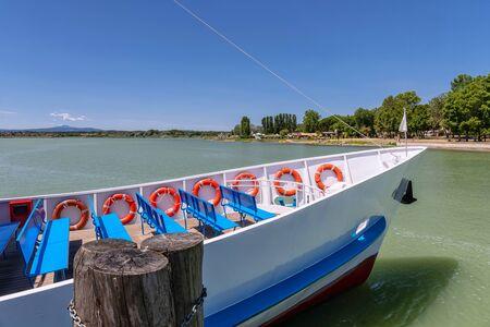 Łódź zacumowana w jeziorze, w słoneczny letni dzień.