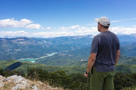 The man looks at the landscape on the horizon, from the top of a mountain. The hiker scrutinizes the mountain landscape and the lake below. On a summer day with cloudy skies. 写真素材