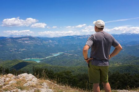 The man looks at the landscape on the horizon, from the top of a mountain. The hiker scrutinizes the mountain landscape and the lake below. On a summer day with cloudy skies. Banco de Imagens