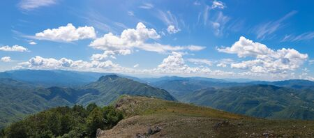 Landscape from the top of the mountains. The horizon between heaven and earth is composed of mountain peaks and a cloudy blue sky. A summer day with sunlight. 写真素材