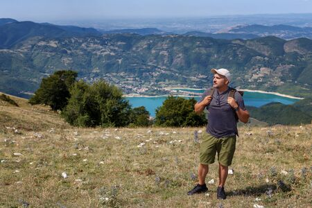 Hiker on the hill, with the backpack on his shoulders. In the background a beautiful landscape of lake and mountains. On a summer day in Italy. Stok Fotoğraf - 132110257