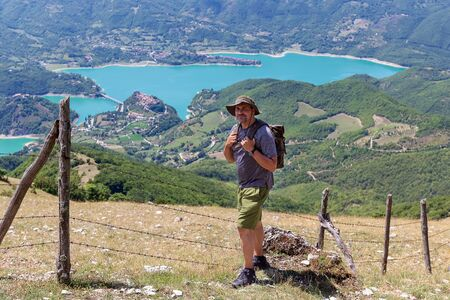 Hiker climbs the hill, wearing a hat and a backpack on his shoulders. In the background a beautiful landscape of lake and mountains. On a summer day in Italy. 写真素材