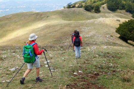 Hikers on the mountain path descend from the top and head downstream. Stok Fotoğraf - 132024487