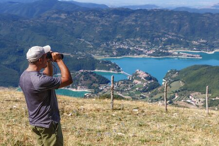 The mountain hiker scrutinizes the landscape landscape on the horizon through the telescope, the valley and the lake below. On a summer day Stok Fotoğraf
