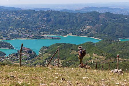 The man looks at the landscape on the horizon, from the top of a mountain. The hiker scrutinizes the mountain landscape, the valley and the lake below. On a summer day