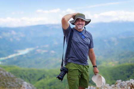 Hiker on the top of the mountains, smiles happily in the middle of nature. Nature photographer during a mountain excursion, on a sunny summer day.