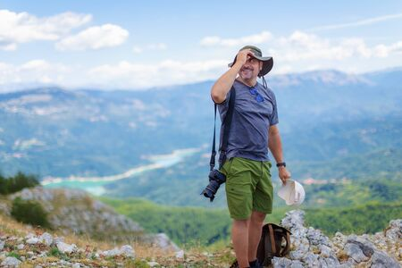 Hiker on the top of the mountains, smiles happily in the middle of nature. Nature photographer during a mountain excursion, on a sunny summer day. Stok Fotoğraf - 132025079