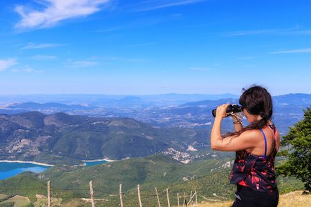 The mountain hiker scrutinizes the landscape on the horizon through the telescope, the valley and the lake below. On a summer day