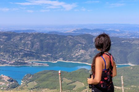 Hiker girl in the mountains scrutinizes the landscape on the horizon, the valley and the lake below. On a summer day Banco de Imagens