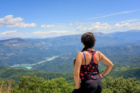 Hiker girl in the mountains scrutinizes the landscape on the horizon, the valley and the lake below. On a summer day. From behind