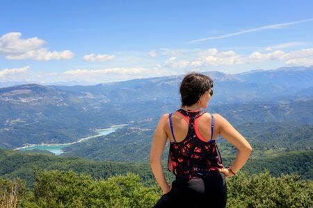 Hiker girl in the mountains scrutinizes the landscape on the horizon, the valley and the lake below. On a summer day. From behind Stok Fotoğraf - 132025849