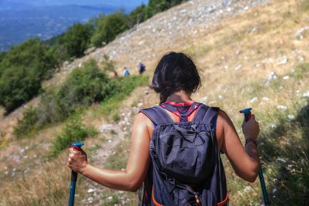 Hiker girl walks on the mountain path, carrying her backpack on her shoulder. On a summer day. From behind