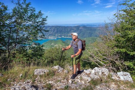 Hiker on the hill, with the backpack on his shoulders. In the background a beautiful landscape of lake and mountains. On a summer day in Italy.