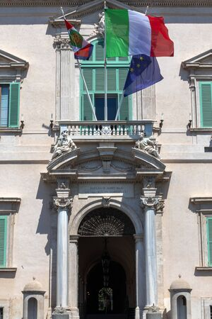 Rome, Italy - August 22, 2019: Quirinale, main entrance of the building, with fluttering flags. Institutional seat of the President of the Italian Republic.