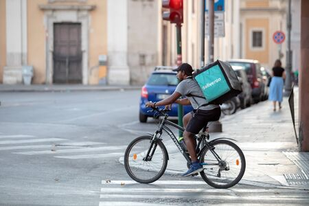 Rome, Italy - August 18, 2019: Boy on a bicycle, carrying food to be delivered to his home. In the city streets.