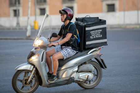 Rome, Italy - August 18, 2019: A boy on a scooter, he transports food to be delivered to his home. In the city streets.