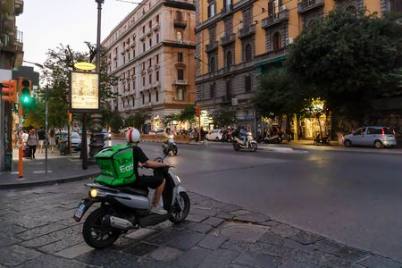 Naples, Italy - August 10, 2019: Uber Eats, a boy with a scooter with the typical green backpack, delivers food at home