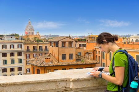 Tourist woman in Rome, consult the map on a panoramic view of the city. From the top of the Trinit? dei Monti stairs, one of the most evocative places to admire the panorama of the capital.