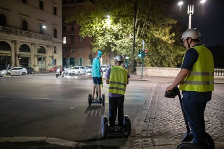 Rome, Italy - 1 September 2019: some young people travel to the city using electric vehicles for alternative mobility. Segway through the city streets lit up at night.
