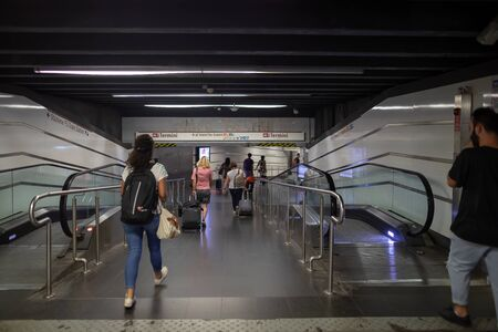 Rome, Italy - 1 September 2019: access ramp to the underground, inside Termini Station. Some people, traveling tourists, go down the escalators to access the trains.