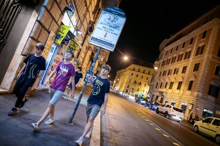 Rome, Italy - September 1, 2019: three boys strolling through the streets of the city, illuminated at night. The truck stop is empty, the busy road.