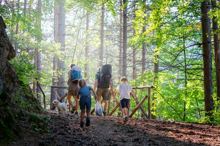 Villetta Barrea (AQ), Italy - September 29, 2019: family with two young children hiking in the woods on the mountain path. Mom, Dad and two children walk on the path in the woods with the backpack on their shoulders. Editöryel
