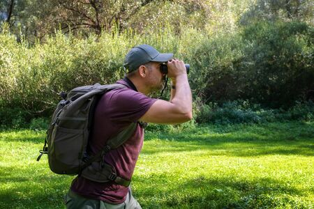 Hiker in the woods lurking in search of wildlife. Man with binoculars peers into the distance looking for wild animals. Outdoors in nature