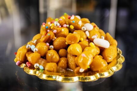 Struffoli, typical Neapolitan pastry consisting of many small balls of dough (realized on paper with flour, eggs, lard, sugar, anise liqueur), fried in oil and wrapped in warm honey. Decorated with colored sprinkles. Stok Fotoğraf