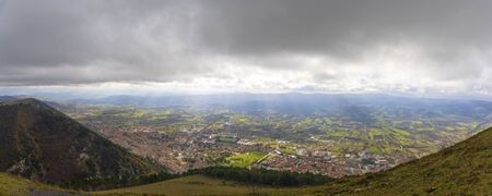Panoramic view of a plain with urban centers, homes, infrastructure and land cultivated in Italy. In the background the mountains and a cloudy sky. Rays of sunlight penetrate the clouds over the plain, on a winter day. Stok Fotoğraf