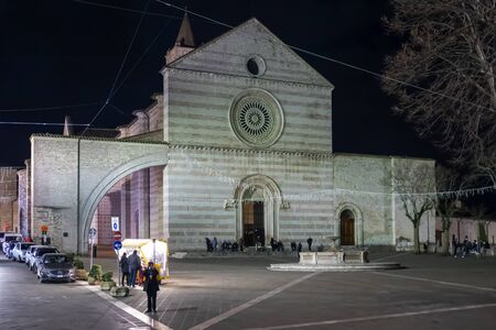 Assisi, Italy - December 7, 2019: The Basilica of Santa Chiara, white and pink front facade with main entrance and square in front. Night view of the church from 1265. Editöryel