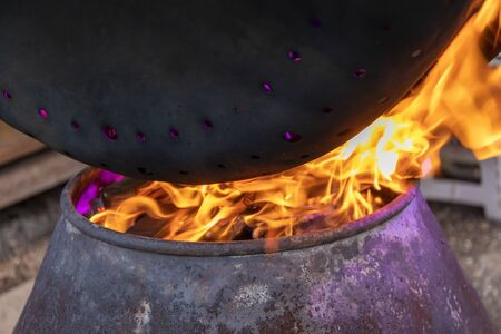 Flame of hot coal heats the perforated pot for cooking chestnuts. Close-up of red flame and burning coal. Stok Fotoğraf