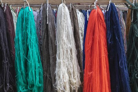 Wool yarns of different colors displayed in a row next to each other. red, green, blue, gray, white, brown woolen threads. group of rows of wool on loom. Stok Fotoğraf