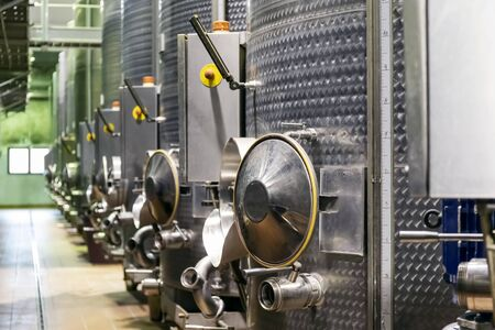 Metal silos for the fermentation of wine inside a farm. Storage of wine in the cellar, after pressing the grapes.