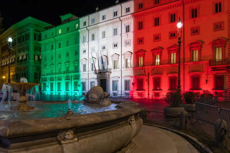 Rome, Italy - March 24, 2020: Palazzo Chigi, seat of the Italian government, facade of the building illuminated with the colors of the Italian flag. Coronavirus emergency Italy.