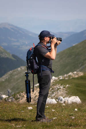 Hiker standing on top of a mountain holds a camera and takes a photograph of the surrounding landscape. The photographer wears hiking clothes with a backpack and tripod. Archivio Fotografico