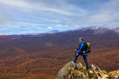 Hiker on top of the rock stops to observe the beautiful autumn landscape of the surrounding mountains.