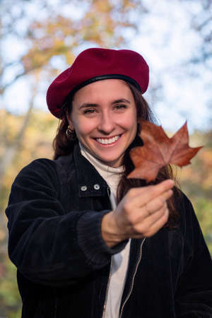 Girl in a red beret offers a dry autumn leaf. Stok Fotoğraf