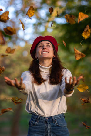 Girl in a red beret throws dry autumn leaves into the air in the woods.
