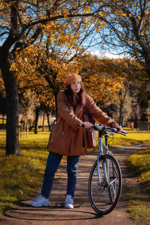 Girl cycling in public park, on the path between the trees with autumn colors