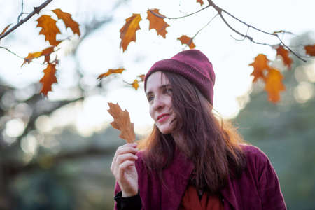 In the autumn season a girl strokes a dry leaf in the public park surrounded by autumn foliage.
