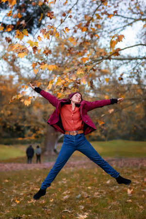 A girl in winter clothes, jeans and a hat, jumps for joy in the foliage of the autumn forest. Stok Fotoğraf