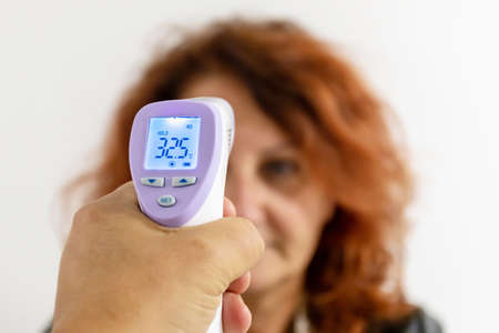 Measure a woman's body temperature using an electronic gun device. Reklamní fotografie