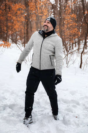 A bearded man in mountain clothes, gray sweatshirt, gloves and hat black, immersed in the snowy forest, rejoices at the falling snowflakes.