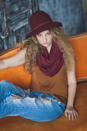 torn jeans: Beautiful curly girl in torn jeans and a scarf
