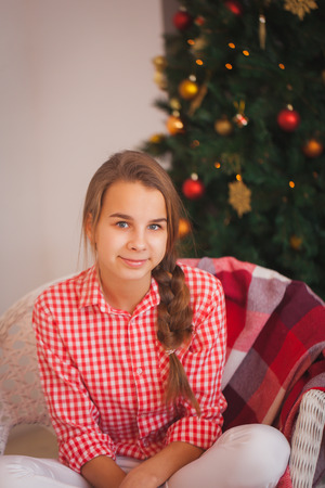 red plaid: Teen girl in a red plaid shirt in Christmas decorations